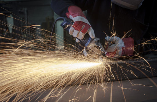 A man grinding a metal workpiece - an example of Glasswork Engineering's fabrication services